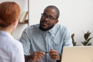 hr manager listening to female applicant asking questions at job interview
